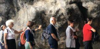 Peregrinos en la gruta de Massabielle en el santuario de Lourdes
